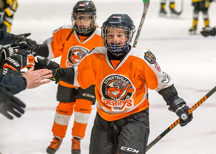 Streetsville Hockey Playing High Fiving Players on the Bench
